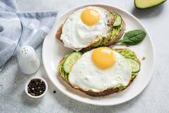 敬酒用鸡蛋、鲕梨和黄瓜在白色板材 免版税库存照片