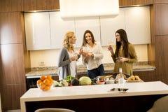 敬酒白葡萄酒的三个妇女朋友在现代厨房里 免版税库存图片