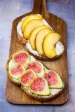 敬酒的三明治用乳脂干酪新鲜的成熟绿色和红色无花果和桃子 下毛毛雨用蜂蜜 整粒黑麦麸皮面包 图库摄影