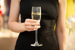 敬酒的妇女拿着杯香槟和,愉快的欢乐片刻 免版税图库摄影