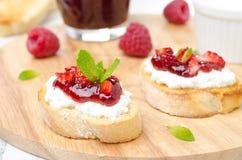 敬酒的长方形宝石用乳脂干酪,山莓果酱,莓 免版税库存图片