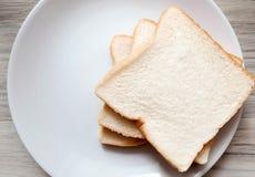 敬酒的面包片在白色板材的 库存照片