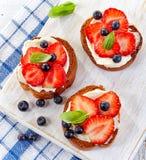 敬酒的面包用乳脂干酪和莓果 免版税库存图片