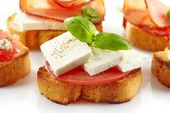 敬酒的面包用新鲜的山羊乳干酪和蕃茄 库存照片