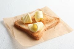 敬酒的面包用新鲜的黄油在桌上卷曲 库存图片