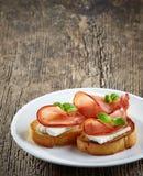敬酒的面包用serrano火腿和新鲜的干酪 免版税图库摄影