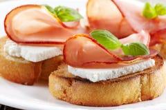 敬酒的面包用serrano火腿和新鲜的干酪 免版税库存图片