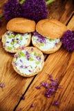 敬酒的面包bruschetta用乳脂干酪和大蒜可食的花在橄榄色的木切板在石蓝灰色的背景 库存图片