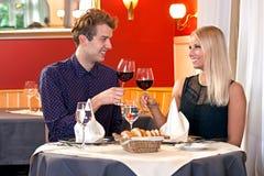 敬酒的年轻夫妇用红葡萄酒 库存图片