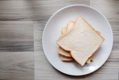 敬酒的3面包片在白色板材的 图库摄影