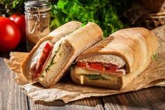 敬酒的panini用火腿、乳酪和芝麻菜三明治 库存图片