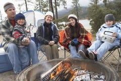 敬酒蛋白软糖的家庭在营火 库存图片