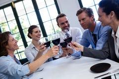 敬酒酒杯的小组买卖人在工作午餐会议期间 库存图片