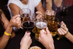 敬酒饮料的朋友在夜总会 免版税库存图片