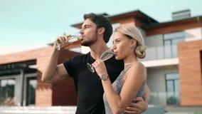 敬酒香槟的可爱的夫妇在豪华公寓附近 影视素材