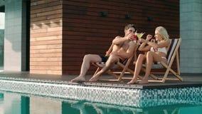 敬酒鸡尾酒的愉快的夫妇在游泳场附近 股票录像