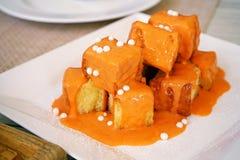 敬酒,方形的面包片断烘烤用黄油,冠上了泰国牛奶茶调味汁和装饰用一小块白色巧克力 免版税图库摄影