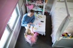 敬酒他们的茶杯的父亲和女孩,当使用与玩具厨房集合时 免版税库存照片