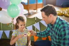 敬酒他们的茶杯的父亲和女孩,当使用与玩具厨房集合时 图库摄影