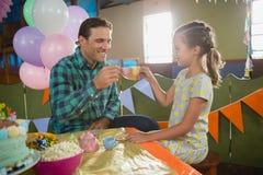 敬酒他们的茶杯的父亲和女孩,当使用与玩具厨房集合时 库存图片