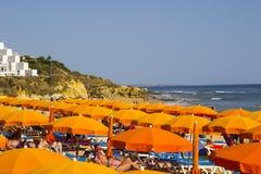 数十把明亮地色的太阳床和沙滩伞在含沙普腊亚Da Oura在Alubferia靠岸在葡萄牙 免版税图库摄影