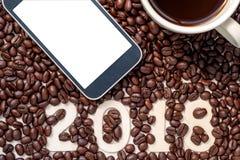 2018数字在与聪明的电话和cof的咖啡豆背景中 免版税库存照片