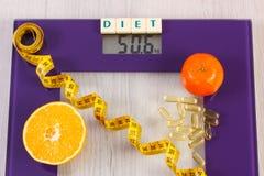 数字式与卷尺的体重计,片剂,果子,减肥概念 免版税库存照片