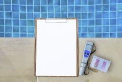 数字式与空白的白皮书的水测试器在木剪贴板 免版税库存照片