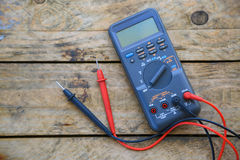 数字式多用电表特写镜头在木背景,工作者的使用了为被检查的电路的电子工具 免版税库存图片