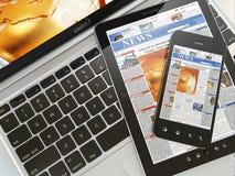 数字式新闻。 膝上型计算机、移动电话和数字式片剂个人计算机 免版税库存照片