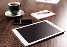 数字式有便条纸和咖啡的片剂计算机在老木书桌上的 免版税库存照片