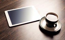 数字式有咖啡的片剂计算机在老木书桌上的 免版税库存图片