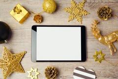 数字式模板的片剂嘲笑与在木背景的圣诞节装饰 在按钮之上上色摇篮表单手机被定调子的查出的银色电话视图可视空白无线 免版税库存照片