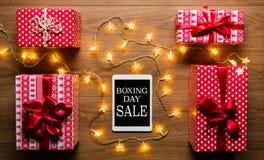 数字式片剂、礼物和圣诞灯,减速火箭的节礼日销售概念 免版税库存图片