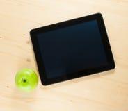 数字式片剂个人计算机和绿色苹果看法上面  库存照片