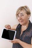 数字式片剂使用由资深妇女 免版税库存照片