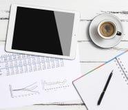 数字式片剂和咖啡杯在木桌上 免版税库存照片