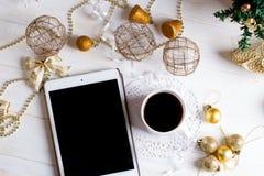 数字式片剂和圣诞节金黄装饰在木backgr 免版税图库摄影