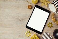数字式片剂和圣诞节金黄装饰在木背景 在视图之上 库存照片