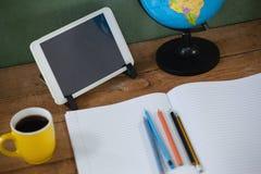 数字式片剂和地球在桌上在教室 图库摄影