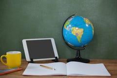 数字式片剂和地球在桌上在教室 免版税库存图片