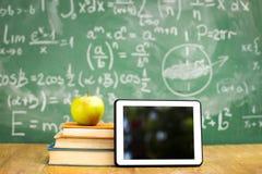 数字式片剂和苹果在堆书 库存图片