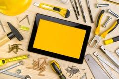 数字式片剂和被分类的木匠业工具在车间表上 库存照片