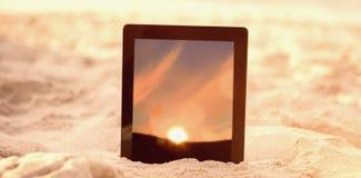 数字式片剂的综合图象在沙子保持了 免版税库存照片