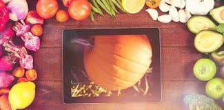数字式片剂的综合图象围拢与新鲜蔬菜 免版税库存图片