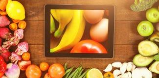 数字式片剂的综合图象围拢与新鲜蔬菜 图库摄影
