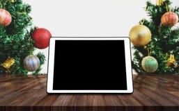 数字式片剂空白黑色屏幕,在有圣诞树和装饰背景的木书桌上 库存图片