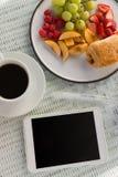 数字式片剂顶上的看法由咖啡杯和果子的 免版税库存照片