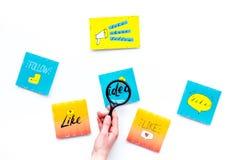 数字式营销 工作营销专家书桌有社会媒介象和标志的 有magnifiger的手在白色 图库摄影