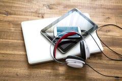 数字式设备和耳机在一个木桌面上 免版税库存照片